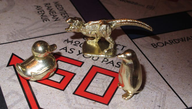 This March 15, 2017 photo shows the three new tokens in Atlantic City, N.J., that fans from around the world have voted into upcoming editions of the board game Monopoly: a duck, a T-Rex dinosaur and a penguin. Hasbro Inc. revealed the results of voting on Friday, March 17, 2017. Leaving the game will be the boot, wheelbarrow and thimble tokens.