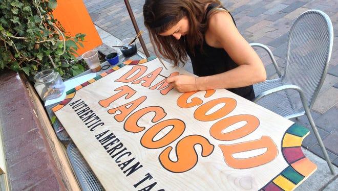 Ali Hatcher paints the sign for Dam Good Tacos. The restaurant is in a trademark dispute with Torchy's Tacos.