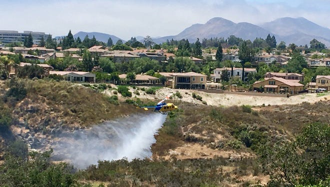 A Ventura County Fire helicopter makes a water drop Friday afternoon in the Lynn Ranch area of Thousand Oaks.