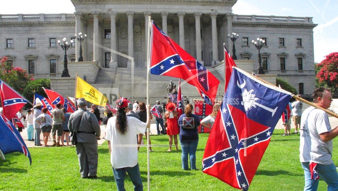 About 50 people, many carrying flags, come for a rally by the South Carolina Secessionist Party at the South Carolina Statehouse on Monday, July 10, 2017, in Columbia, S.C. The group raised a Confederate flag on a temporary pole to mark two years since the day the flag was removed from the front lawn of the state capitol. (AP Photo/Jeffrey Collins) The Secessionist Party says it will raise the flag every July 10th so a year will never go by without the Confederate flag flying. (AP Photo/Jeffrey Collins)