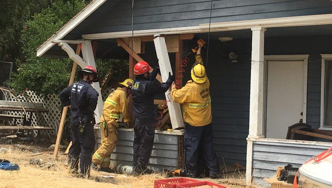 Ventura County firefighters and others shore up a front porch of a home after it was hit by a vehicle in Piru on Wednesday morning.