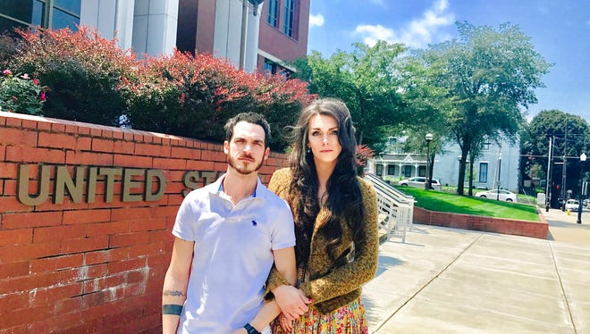 This Aug. 4, 2017, photo provided by Jillian Weiss shows Dane Lane, left, and his transgender wife, Allegra Schawe-Lane, outside the federal courthouse in Covington. The couple is filing a lawsuit against Amazon, alleging that they endured sustained discrimination and harassment during a year as co-workers at an Amazon warehouse in Kentucky. (Jillian Weiss via AP)