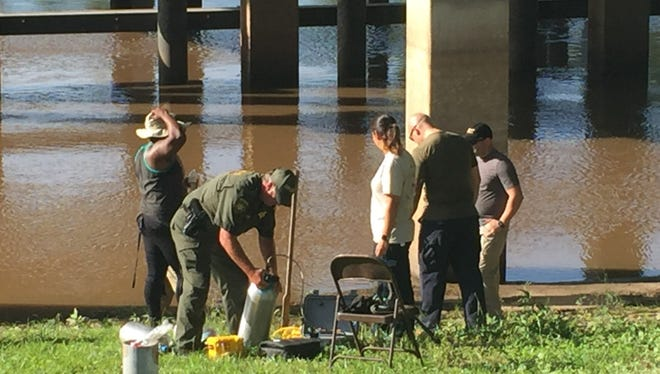 Lafayette Parish sheriff's deputies and volunteer groups search the Vermilion River at River Ranch in hopes of discovering what two cadaver dogs alerted as something of suspicion in the river.