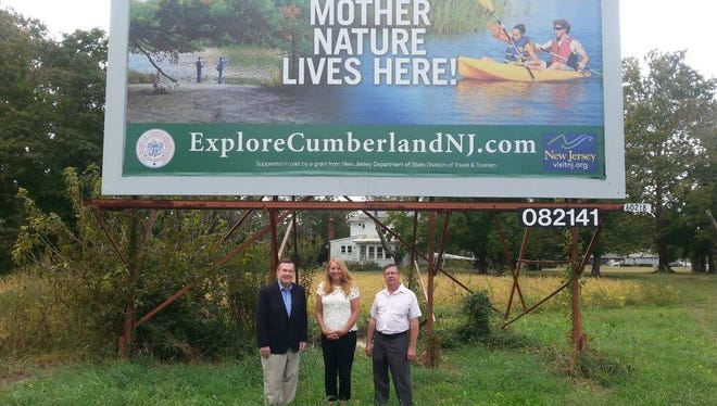 """(From left) Cumberland County Freeholder Jim Quinn, Kim Gauntt, director of Tourism and Recreation for Cumberland County, and Joe Deluca, chairman of the Cumberland County Tourism Advisory Council, show off one of the new """"explorecumberlandnj"""" billboards."""