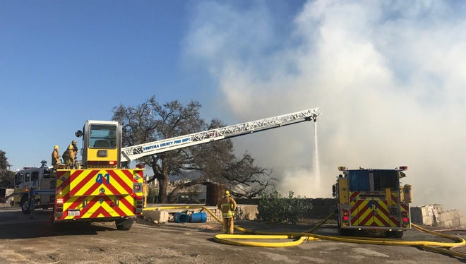 A Ventura County fire ladder truck douses a trash fire in Simi Valley Friday evening.