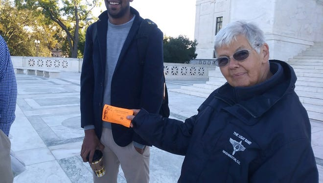 Allison Seaton, right, displays her ticket to attend arguments in the case Gill v. Whitford at the U.S. Supreme Court on Oct. 3, 2017.