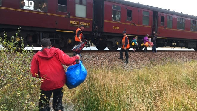 In this photo taken on Friday, Oct. 13, 2017, children run towards a train near Loch Eilt in  the Scottish Highlands. As if by magic, the Hogwarts Express has come to the rescue of a stranded family in Scotland. The train that took Harry Potter and his friends to school was played onscreen by the Jacobite steam train in the Scottish Highlands. On Friday it made an unscheduled stop to pick up a family of six that was stranded when their canoe was washed away in a storm. (Jon Cluett via AP)