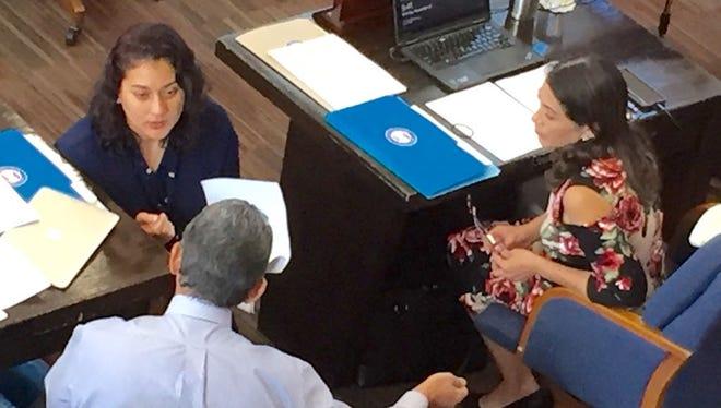 Sen. Telena Nelson confers with Sen. Tom Ada while Sen. Mary Torres looks on during a Nov. 27 legislative session.