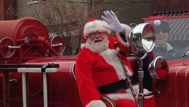 Ed Ulsas dressed as Santa waves while riding along Fairfield Avenue in Bellevue in an antique fire truck.