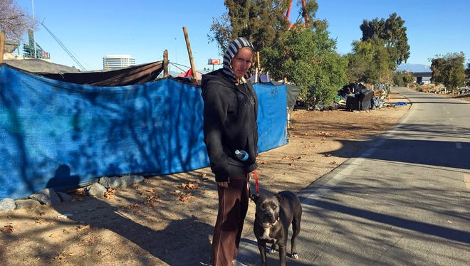 Heather Smith, a 42-year-old homeless woman, stands with her pit bull, She-Ra, outside her tent on the riverbed trail in Anaheim, Calif., Monday, Jan. 22, 2018. Smith doesn't know where she'll go now that Orange County authorities are moving to clear the riverbed encampment where she lives.