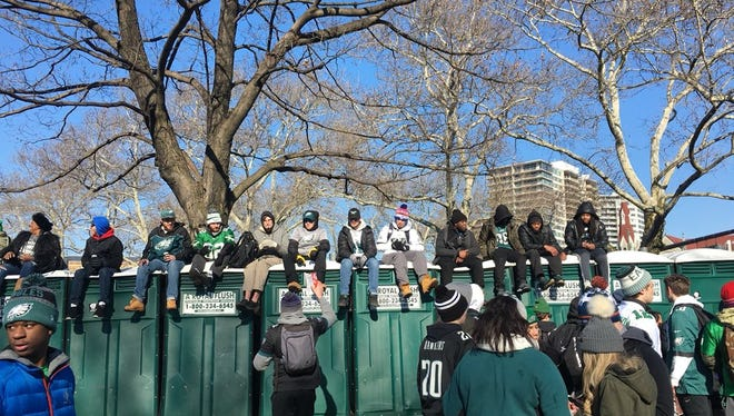 Eagles fans try to get a better vantage point for a celebratory parade in Philadelphia Thursday.