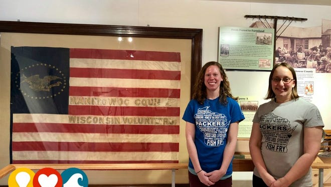 Amy Meyer, executive director (left), and Alex Brendemuehl, program coordinator, pose in front of a display at the Manitowoc County Historical Society.