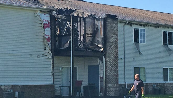 A firefighter surveys damage from a morning fire at the Camby Crossing Apartment Homes in the 7400 block of Camby Crossing, Tuesday, June 5, 2018.