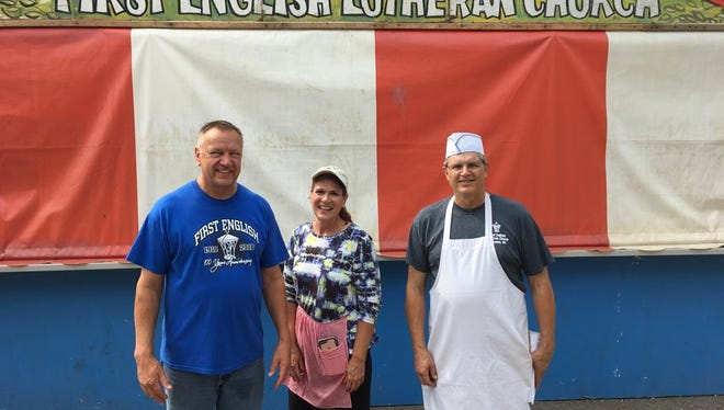 Neil Juedes, left, Linda Betzner and Scott Kufahl pose for a picture outside the First English Lutheran Church stand on Saturday morning at the Wisconsin Valley Fair.