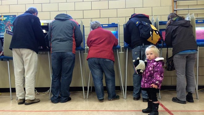 Two-year-old Amelia Thayer waits as her parents vote at Longfellow Elementary in Iowa City