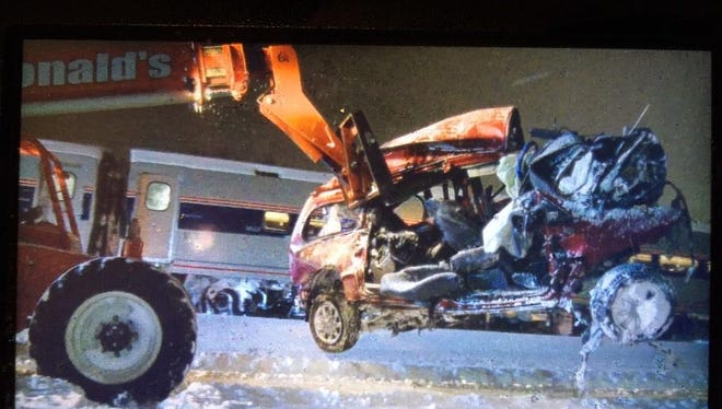 Crews remove a minivan struck by a train in Kalamazoo. Three people in the minivan died.