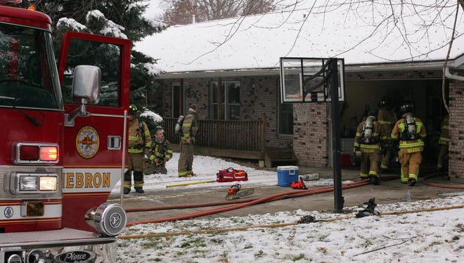 Firefighters work to extinguish a fire at a home on Freeman Memorial Drive in the Harbor Hills subdivision near Buckeye Lake.