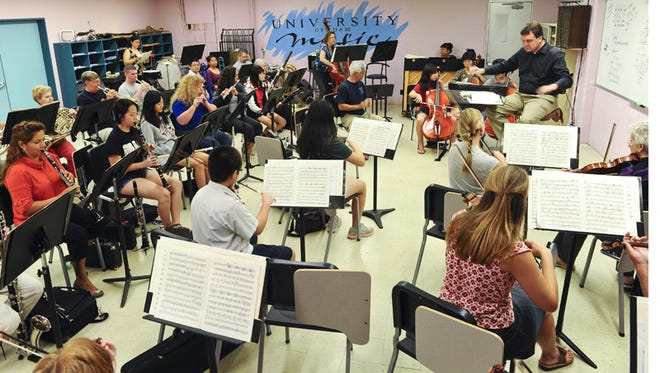 In this May 12, 2014, file photo, members of the Orchestra for the Guam Symphony Society rehearse.