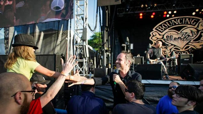 Bouncing Souls frontman Greg Attonito steps offstage to greet his fans, including Elora Burke, 11, of Mt. Pleasant, a student bassist who was really focused on the bass guitar, Wednesday, July 6, 2016 during the Common Ground Music Festival at Louis Adado Riverfront Park in downtown Lansing.