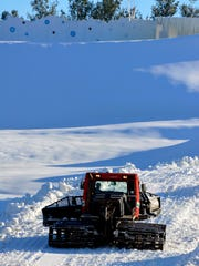 A snow groomer preps the tubing hill at AvalancheXpress