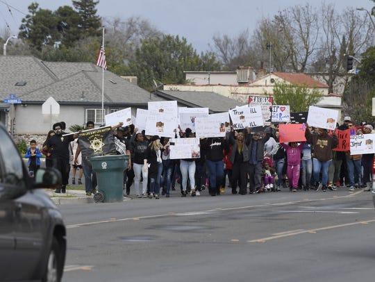Marchers walk down Cross Avenue in Tulare to promote