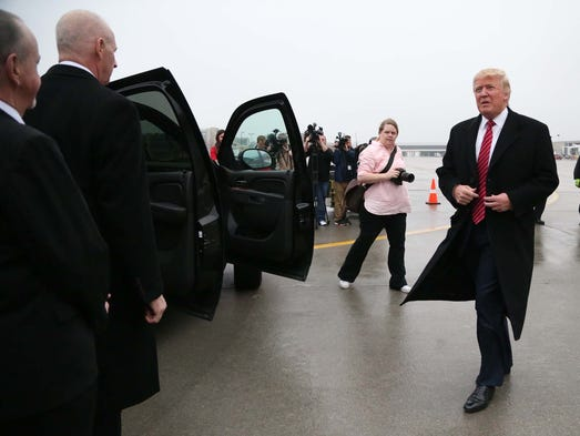 Donald Trump walks from his plane to a car taking him to his next ...