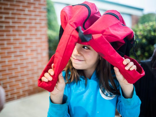 Second grader, Mariah Mendez, holds her backpack over her head to shield herself from the rain while waiting in the carpool line during an early release at Nevitt Forest Elementary School on Wednesday, April 5, 2017 in Anderson.