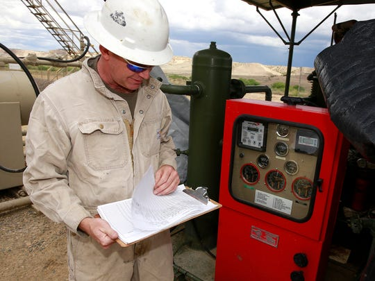 Tom Mullins, owner/operator of Synergy Operating LLC, looks over the maintenance logbook for a compressor that provides electricity at one of the company's shut-in gas well sites on May 17 near La Plata Highway and Twin Peaks Boulevard.
