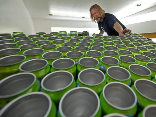 Rob Pfeiffer, then-head brewer for Twin Lakes Brewing Company, helps place empty beer cans on a distribution machine for filling in 2011.