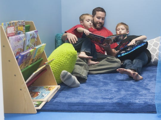 Charlie LaRochelle, who owns We Rock The Spectrum Kid's Gym For ALL Kids - Mount Laurel with his wife, Julie, reads with his sons Shane, 4, left, and Chase, 8, in the gym's calming room.