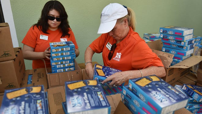"Treasure Coast Food Bank staff members Ruby Aguirre (left) and Wendie Berardi unpack cases of food during the food bank's Hurricane Disaster Relief food distribution at the Indiantown Non-Profit Housing office on Sept. 20, 2017, in Indiantown. ""People are hungry, no one should be hungry in America,"" Berardi said while helping the Treasure Coast Food Bank provide hundreds of families with food donations during the distribution."
