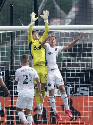 Vancouver goalkeeper Thomas Hasal and Chicago player Robert Beric (22) leap for the ball during the MLS is Back Tournament at Disney's ESPN Wide World of Sports complex Thursday in Orlando.