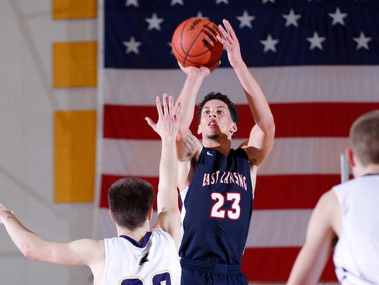 East Lansing's Brandon Johns shoots against DeWitt's