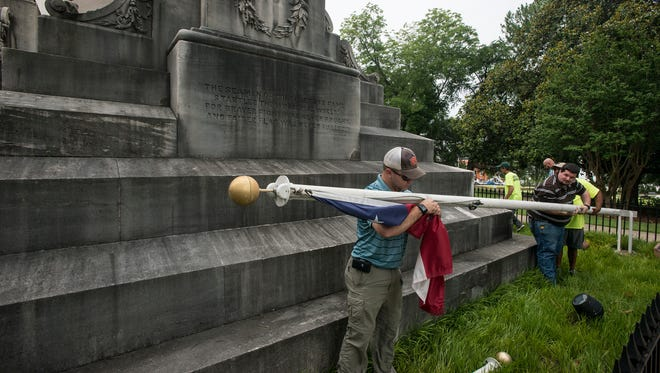 Workers remove the Confederate flags from outside the State Capitol building on Wednesday, June 24, 2015.