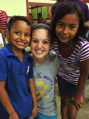 Jackson Christian student Allie Myers (middle) poses with two children during a mission trip to León, Nicaragua.