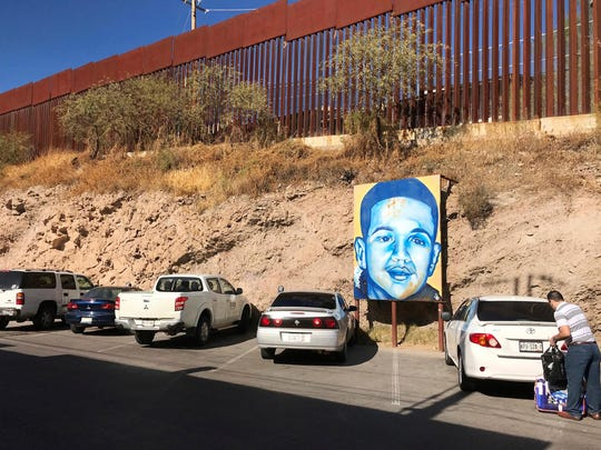 This file photo taken Monday, Dec. 4, 2017 shows the boundary in Nogales, Mexico, with the United States and a poster of Juan Antonio Elena Rodriguez, a teen who was shot and killed across the line by a Border Patrol agent in 2010.
