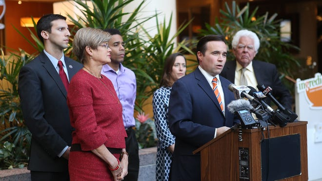 Cincinnati Mayor John Cranley speaks with Port Authority head Laura Brunner as they announce that the parking plan is suspended at the Westin Hotel on Tuesday, November 12, 2013. In addition to Cranley, four Cincinnati city council-elects attended the conference in support. From left to right is councilman P.G. Sittenfeld, Port Authority head Jennifer Bruner, councilman Christopher Smitherman, council-elect Amy Murray, and council-elect David Mann.
