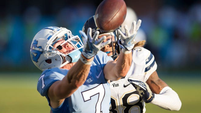North Carolina Tar Heels wide receiver Austin Proehl (7) catches a pass while being defended by Pittsburgh Panthers defensive back Ryan Lewis (38) during the third quarter at Kenan Memorial Stadium.
