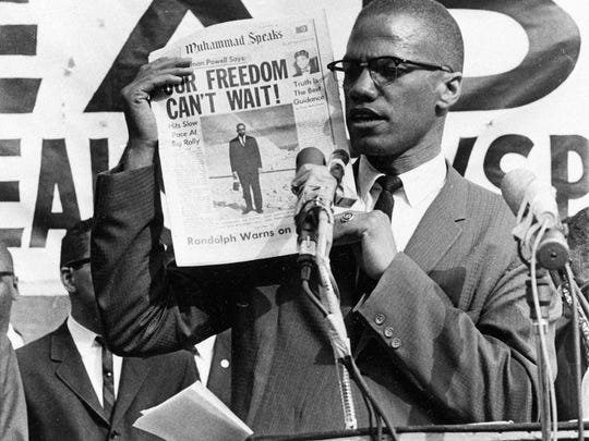 Black Muslim leader Malcolm X holds up a paper for