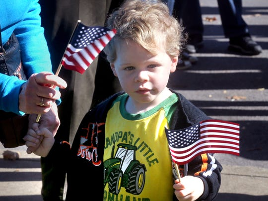 Michael Traghber, 3, waves American flags before the start of the Veterans Day Memorial Service on the Square in Murfreesboro on Wednesday.