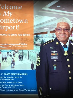 A 6-foot by 6-foot display with Medal of Honor recipient Melvin Morris' photo hangs in a prominent place at Orlando International Airport.