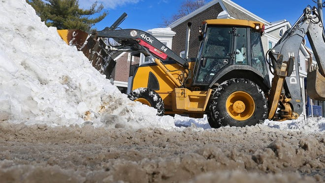 City of Wilmington's Public Works department work on removing snow from this past weekends massive storm from Washington and W. St.  Monday morning