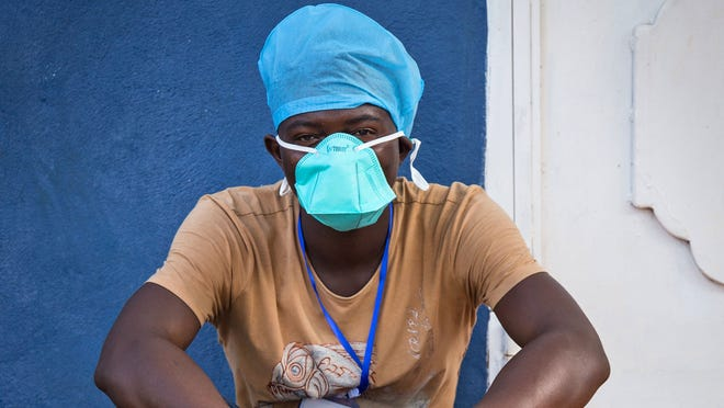 In this Sept. 19, 2014 photo, an Ebola virus health care worker takes a rest outside a Ebola isolation unit in Freetown, Sierra Leone.