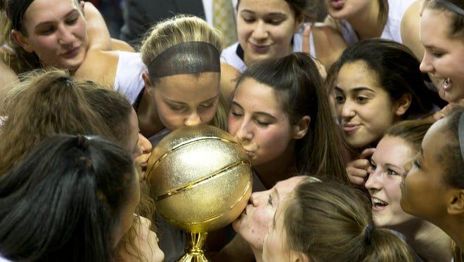 St John Vianney players celebrate by kissing their trophy. SJV vs Manasquan Girls  Basketball Tournament of Champions Final in Trenton NJ on March 21, 2016