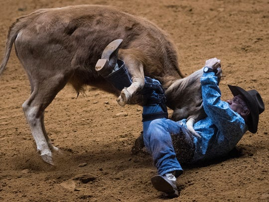 Payton Caudill competes in steer wrestling during the