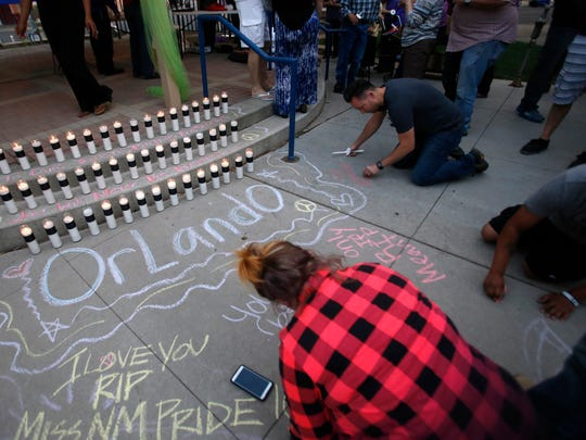 At a vigil on Monday evening at Orchard Park in Farmington, community members write messages of support for the victims of a mass shooting at a nightclub in Orlando, Fla.