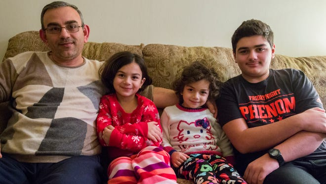 Marwan Batman (from left), Raghad, Remas and Rakan sit on their sofa in their Northeastside apartment on November 21, 2015.