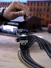 Fred Rogge's hand hovers over a locomotive as he monitors the train's progress through the room Saturday. The Abilene Society of Model Railroaders has more than 800 feet of track set up in its new location at 598 Westwood. Trains of 15 or more cars travel through a range of simulated terrain and cityscapes.