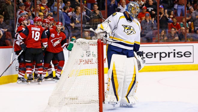 Nashville Predators goalie Pekka Rinne (35) pauses in front of the net after giving up a goal to Arizona Coyotes left wing Brendan Perlini as Perlini celebrates with center Christian Dvorak (18) and other players during the second period on Dec. 10, 2016.