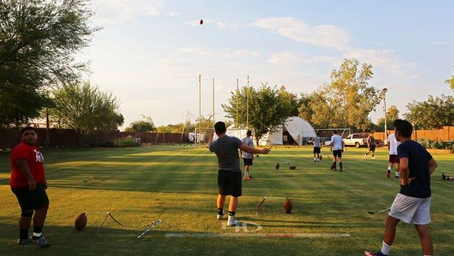 High school players take turns kicking field goals on a 60-yard field built in the backyard of former professional kicker Luis Zendejas.